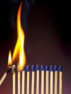 a lit match ignites a row of other matches