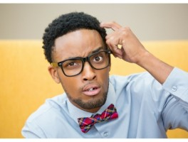 Man wearing glasses, a blue shirt and red patterned bowtie, scratching his head with a confused look on his face