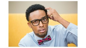 Man wearing glasses and a blue shirt and red patterned bowtie scratching his head with a confused facial expression
